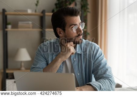 Pensive Young Business Man In Eyeglasses Looking In Distance.