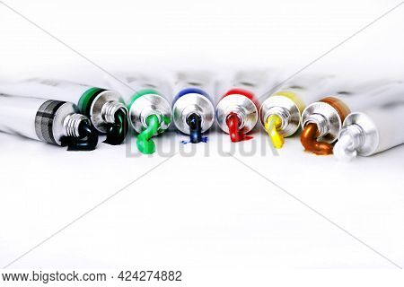 Colorful Tubes Of Oil Paints Spilling Shiny Paint Out Onto A White Background