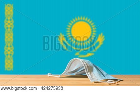 A Medical Mask Lies On The Table Against The Background Of The Flag Of Kazakhstan. The Concept Of A