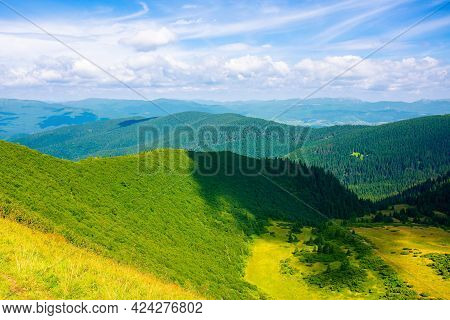 Grass On The Steep Hill. View In To The Distant Valleys And Gorgany Ridge Beneath A Blue Sky With Cl