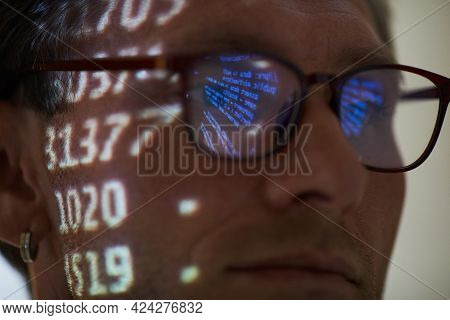 Close-up Of Computer Hacker In Eyeglasses Working With Computer Code Reflecting In His Eyeglasses