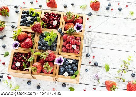 Top Down View Of A Wooden Compartment Box Filled With Various Types Of Berries And Berries All Aroun