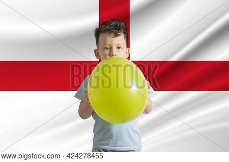 Children's Day In England. White Boy With A Balloon On The Background Of The Flag Of England. Childr