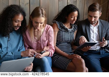 Smiling Young Mixed Race People Using Different Device.