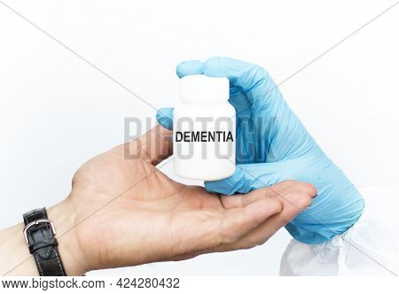 The Doctor's Hand In The Glove Transfers A Jar Of A Text Dementia To The Patient's Hand On A White B