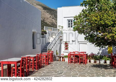 Tavern Cafe Seats Tables Cobblestone Yard Background At Sifnos Island, Greece.