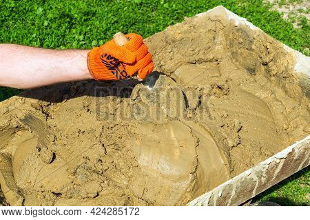 Mix The Cement With Sand And Water With A Trowel. Builder Is Hand In A Glove With A Trowel During Wo