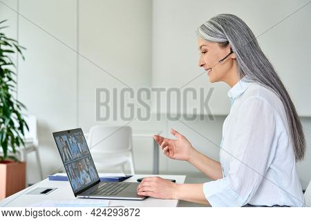 Happy Smiling Older Asian Businesswoman Ceo Executive Manager In Headset On Corporate Videoconferenc