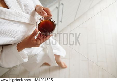 Top View Of Cup With Coffee In The Hands Of A Woman In White Waffle Bathrobe Standing At The House K