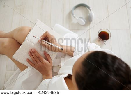 An Overhead View Of A Brunette Woman Sitting On The Floor And Writing In A Notebook. Cup With Coffee