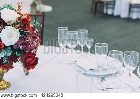 Fancy Table Set For Dinner With Flower Composition In Restaurant, Luxury Interior Background. Weddin