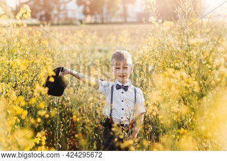 A Little Boy Plays With A Hat In An Oilseed Rape Field