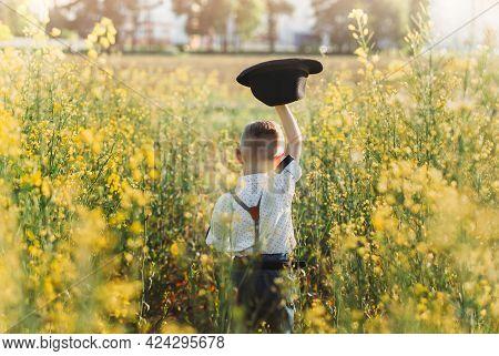 A Little Boy Holds A Hat And Runs On An Oilseed Rape Field. Rear View