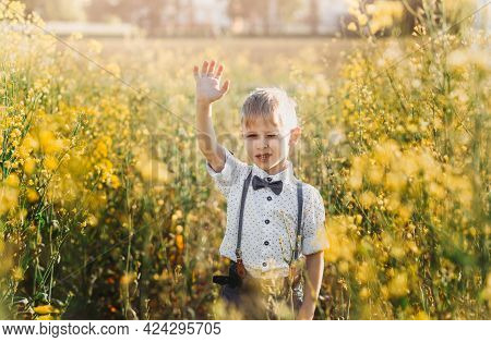 Little Boy Having Fun And Waves His Hand To The Camera In Nature In The Summer. Cute Adorable Child