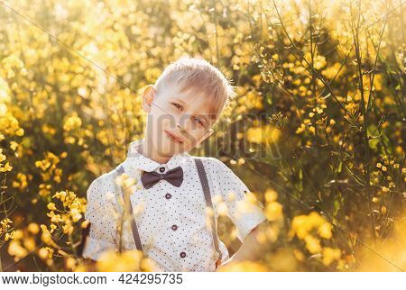 Little Cute Boy In An Oilseed Rape Field. Rural Landscape