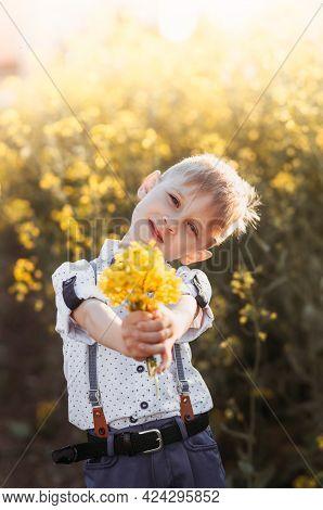 Little Cute Boy In An Oilseed Rape Field. Rural Landscape. Vertical