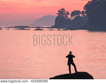 Unrecognizable Person Taking Photo With Mobile At Sunset On A Rock To The Cies Islands In Spain