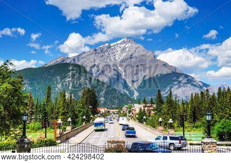 Busy Banff Avenue Inside Banff National Park With Cascade Mountain In The Background. The Town Is A