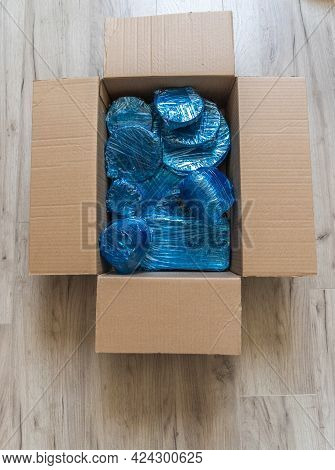 Glassware Wrapped With Blue Wrapping Nylon At The Bottom Of A Cardboard Box. Glassware Wrapped In A