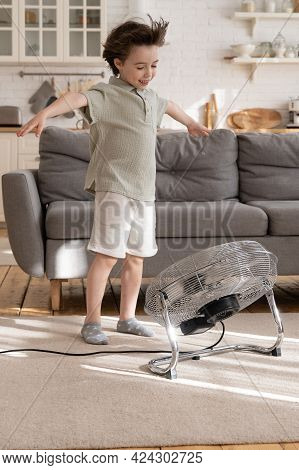 Playful Small Kid Alone In Living Room Enjoy Fresh Cool Breeze Blowing From Big Industrial Retro Ven