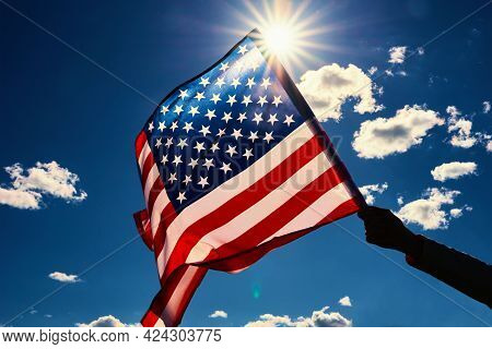 Waving American Flag Outdoors. Hand Holds Usa National Flag Against Blue Cloudy Sky. Memorial Day An