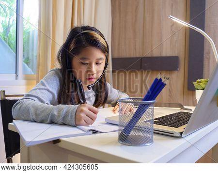 Asian Girl In Headphones Sit At Desk Study Online On Laptop. Kid Wear Headset Handwriting In Noteboo