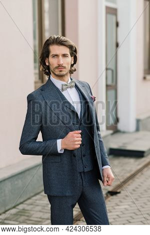 Handsome Fashion Businessman Model Dressed In Elegant Suit And Posing On Street. Metrosexual