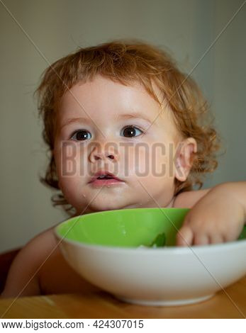 Happy Baby Eating Himself With A Spoon. Healthy Nutrition For Kids. Funny Child Face Closeup.