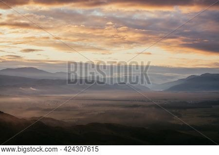 Scenic Mountain Landscape With Golden Low Clouds Above Village Among Mountains Silhouettes Under Daw