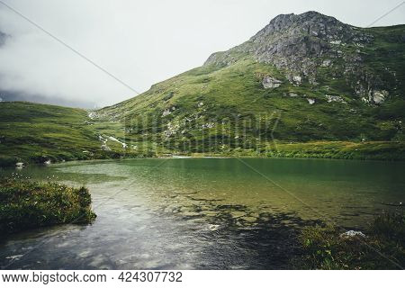 Atmospheric Mountain Landscape With Rainy Circles On Clear Lake Water. Sandy Bottom Of Mountain Lake