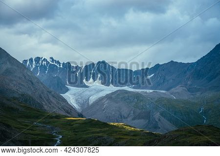 Spot Of Sunlight On Mountains In Overcast Weather. Dramatic Landscape With Big Glacier Under Cloudy