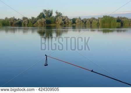 Fishing Rod With Silver Bell Against Background Of River. Selective Focus.