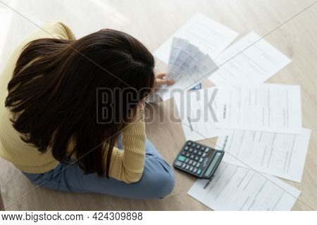 Women Stress About A Lot Of Credit Card Debt And Bills On The Floor. The Housewife Has Trouble Calcu