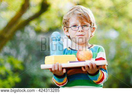Confused Upset Little Preschool Boy With Books, Apple And Drink Bottle On His First Day To Elementar