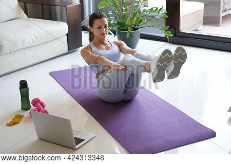Attractive Slim Girl In Sportswear Is Doing Abs Exercise On The Floor At Home. Healthy Lifestyle.