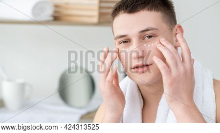 Moisturizing Cream. Male Skincare. Facial Cosmetology. Peaceful Joyful Shirtless Young Man Applying