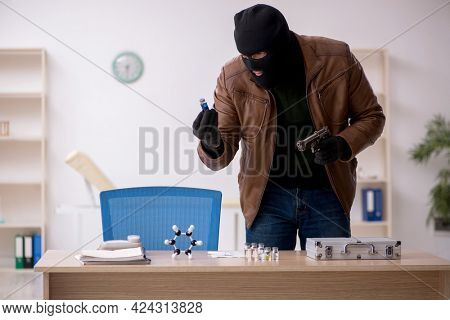 Young man in balaclava stealing vaccine from the lab