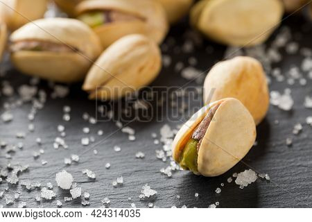Macro Of Salted, Roasted Green Pistachio Nuts Snack On Black Background With Sea Salt, Healthy Food