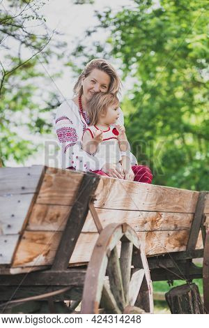 Beautiful Peasant Woman In Embroidered Clothes Sits With Her Daughter On A Cart