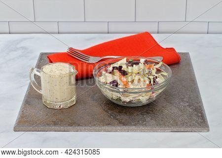 A Glass Bowl Of Fresh Cole Slaw, With A Side Of Dressing On A Slate Tile On A Table.