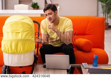 Young man looking after new born at home