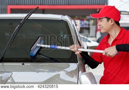 Asian Gas Station Worker In Red Uniform Cleaning The Car Windshield With Window Squeegee.