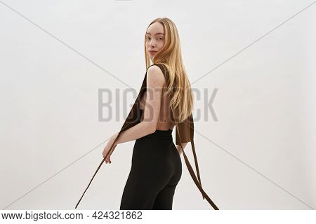 Seductive Young Caucasian Woman In Knitted Top On Naked Breasts Posing Sideways On Light Background
