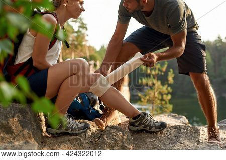 Young Caucasian Man Putting Elastic Bandage On Injured Woman Knee During Hiking In Summer Nature, Cr