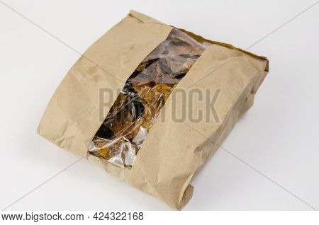 Pet Treats In A Brown Paper Bag With A Window. Kraft Bag With Pieces Of Dried Cows Udders On A White