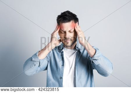 Man Suffering From Terrible Migraine On Light Grey Background