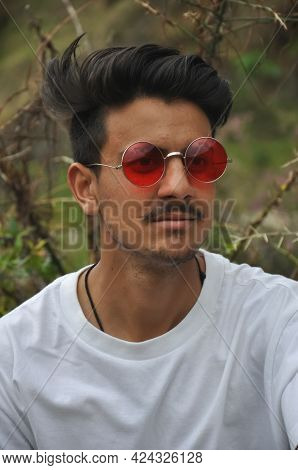 Closeup Of A North Indian Guy Wearing White Tshirt And Red Sunglasses Sitting Outdoor With Looking S