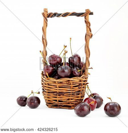 Wicker Basket Full Of Ripe Sweet Cherries On White Background