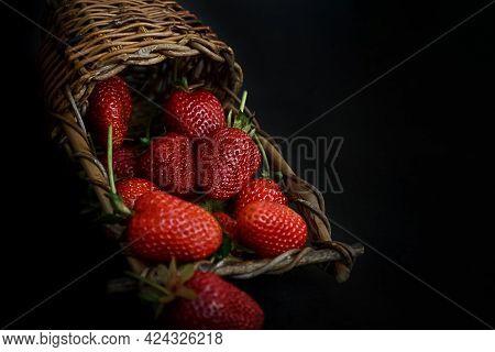 Wicker Basket Lays On Dark Surface Full Of Red Ripe Srtawberries, Summer Food Background