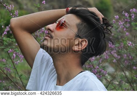 Side View Of A Indian Young Guy Wearing White T-shirt And Red Color Sunglass With Passing His Hand T